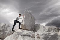 man pushing large boulder